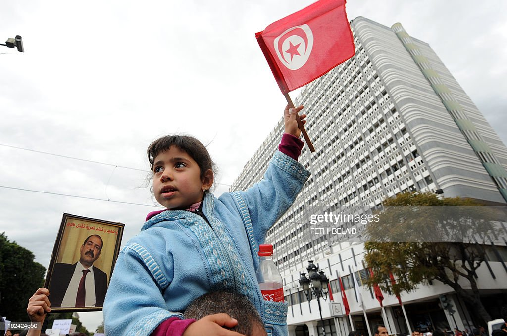 A Tunisian young girl waves a national flag during a demonstration on February 23, 2013 on the Habib Bourguiba Avenue in Tunis. Hundreds of demonstrators marched to protest against the Islamist party Ennahda in power, and demanded that opposition leader Chokri Belaid's killers be found. At background, Belaid is featured on the placard.