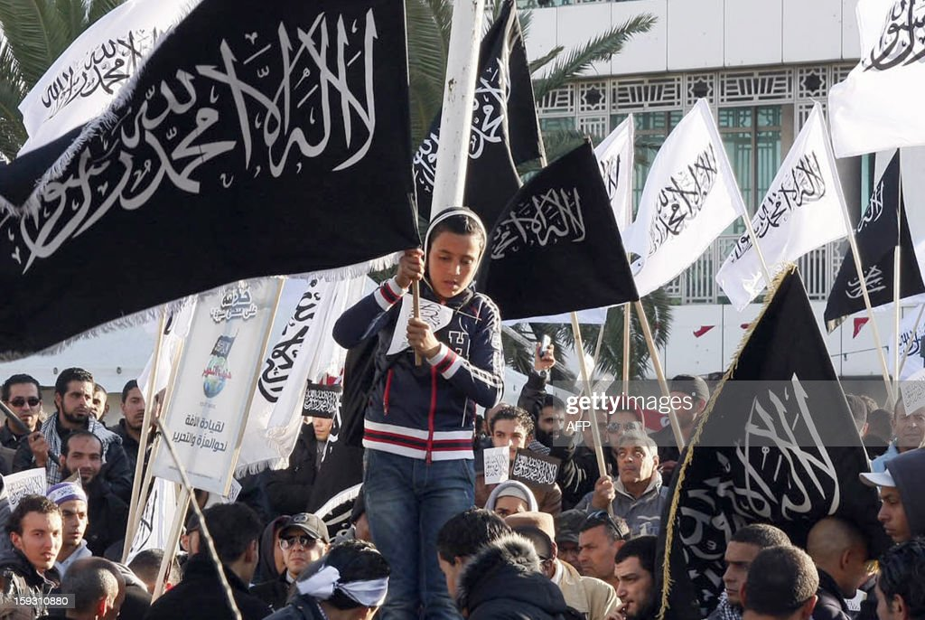 A Tunisian young holds a flag reading 'There's no God but God and Mohammed is his prophet' during a demonstration of the Tunisian Islamist party Hizb Ettahrir outside the National Constituent Assembly to demand the application of the Islamic sharia law on January 11, 2013 in Tunis. AFP PHOTO / KHALIL