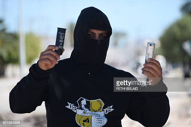 A Tunisian youth shows tear gas canisters that he collected on the ground as he stands on a road that residents blocked to prevent the police and...
