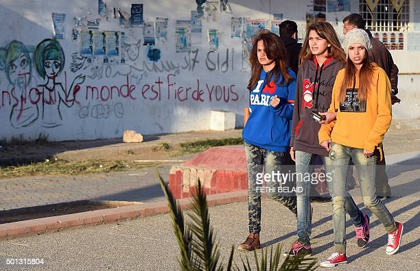 Tunisian youth walk on Mohamed Bouazizi Avenue on December 14 in the impoverished central town of Sidi Bouzid a few days ahead of the fifth...