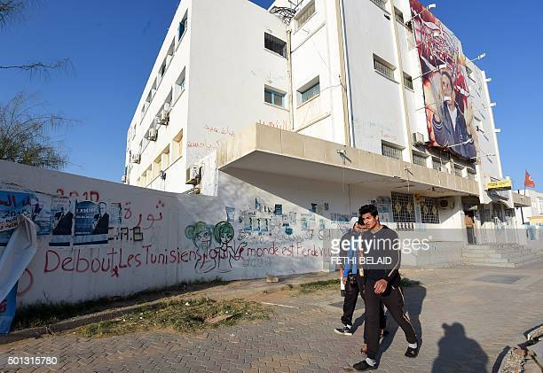 Tunisian youth walk past a giant poster showing Mohamed Bouazizi a young street vendor whose selfimmolation sparked the revolution that ousted a...