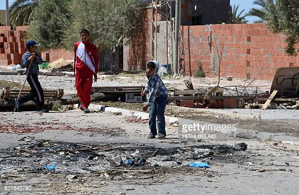 Tunisian youths play next to a makeshift road block in the locality of Laataya on the island of Kerkennah on April 15 2016 after residents blocked a...