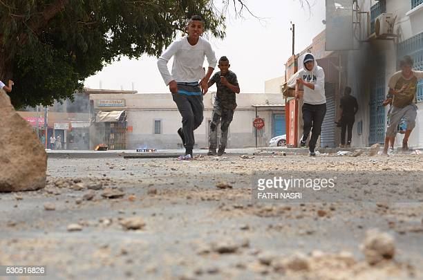 Tunisians boys run away as they throw stones towards the police station on May 11 2016 in the Tunisian southern border town of Ben Guerdane as the...