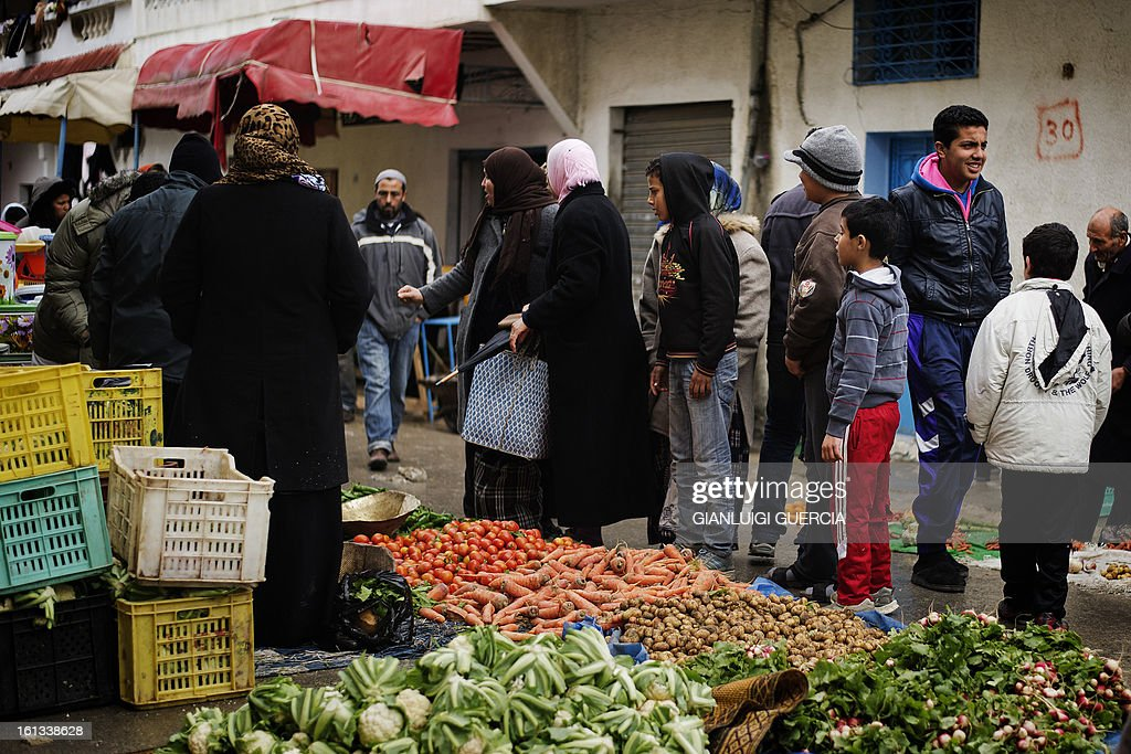 Tunisians buy vegetables from a street vendor at a local market in the Kabaria neighbourhood on the outskirts of Tunis on February 10, 2013. After clashes with demonstrators that the interior ministry said left one policemen dead and 59 colleagues wounded, security forces remain on a state of alert with the army deployed nationwide.