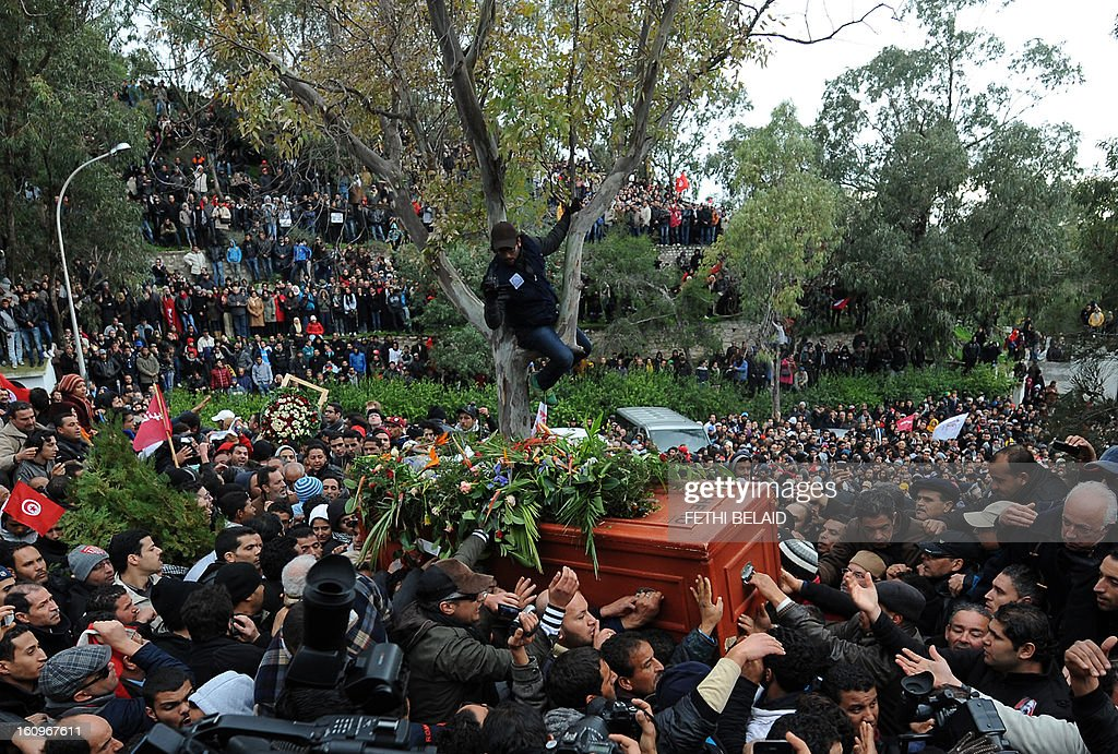 Tunisians carry the coffin of assassinated opposition leader Chokri Belaid ahead of his burial at El-Jellaz cemetery in a suburb of Tunis on February 8, 2013. Tunisian police fired tear gas and clashed with protesters as tens of thousands joined the funeral of Belaid whose murder plunged the country into new post-revolt turmoil.