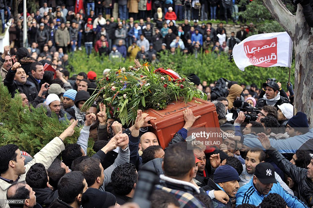 Tunisians carry the coffin of assassinated opposition leader Chokri Belaid ahead of his burial at El-Jellaz cemetery in a suburb of Tunis on February 8, 2013. Tunisian police fired tear gas and clashed with protesters as tens of thousands joined the funeral of Belaid whose murder plunged the country into new post-revolt turmoil. AFP PHOTO/FETHI BELAID