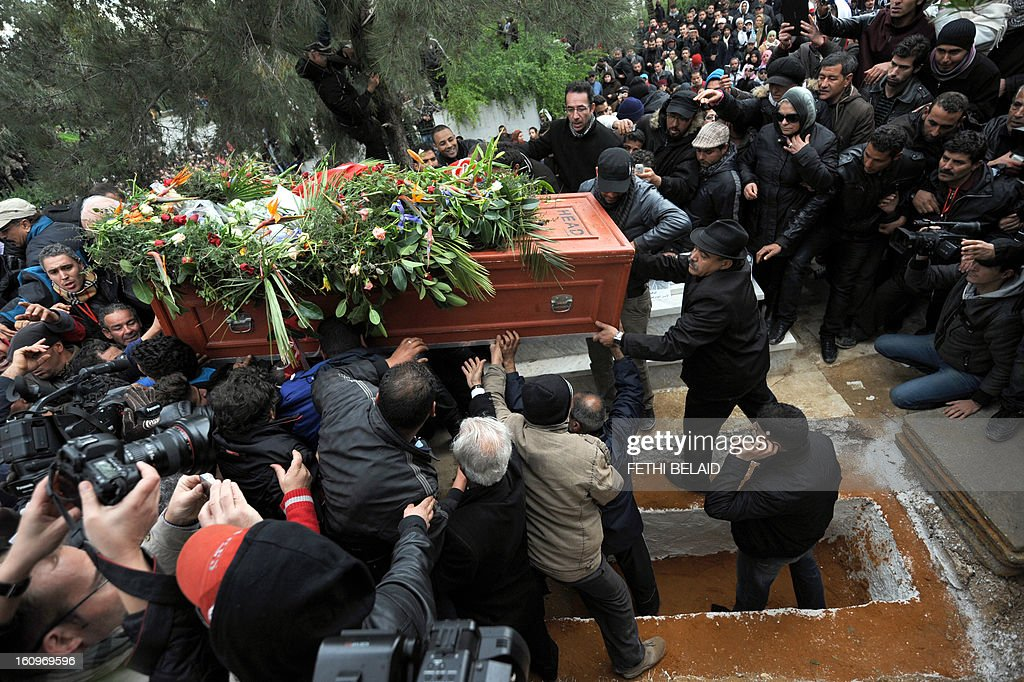 Tunisians carry the coffin of assassinated opposition leader Chokri Belaid during his burial at El-Jellaz cemetery in a suburb of Tunis on February 8, 2013. Tunisian police fired tear gas and clashed with protesters as tens of thousands joined the funeral of Belaid whose murder plunged the country into new post-revolt turmoil.
