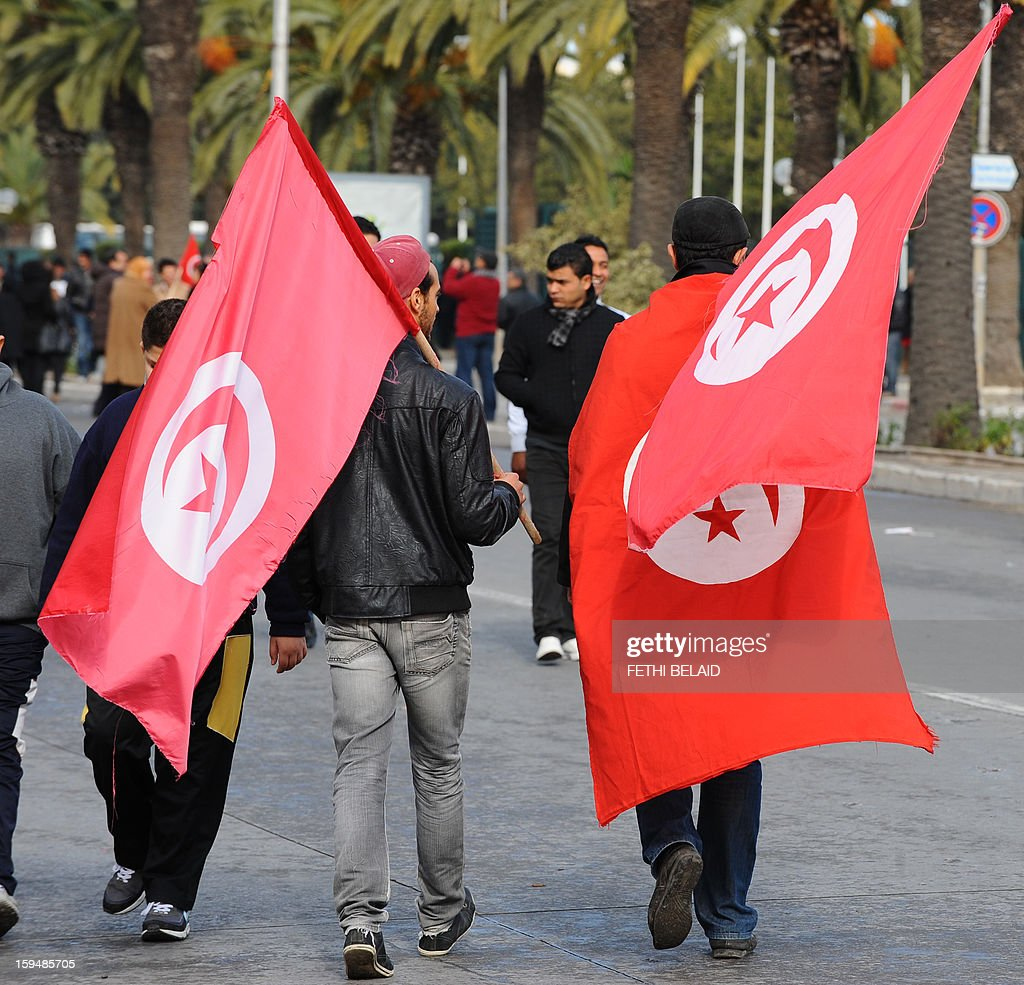 Tunisians hold national flags during a gathering as part of the festivities marking the second anniversary of the uprising that ousted long-time dictator Zine El Abidine Ben Ali on January 14, 2013 in Tunis. Tunisians marked two years since the revolution amid a climate of uncertainty marked by social tension, a weak economy, threats from jihadists and a political impasse.