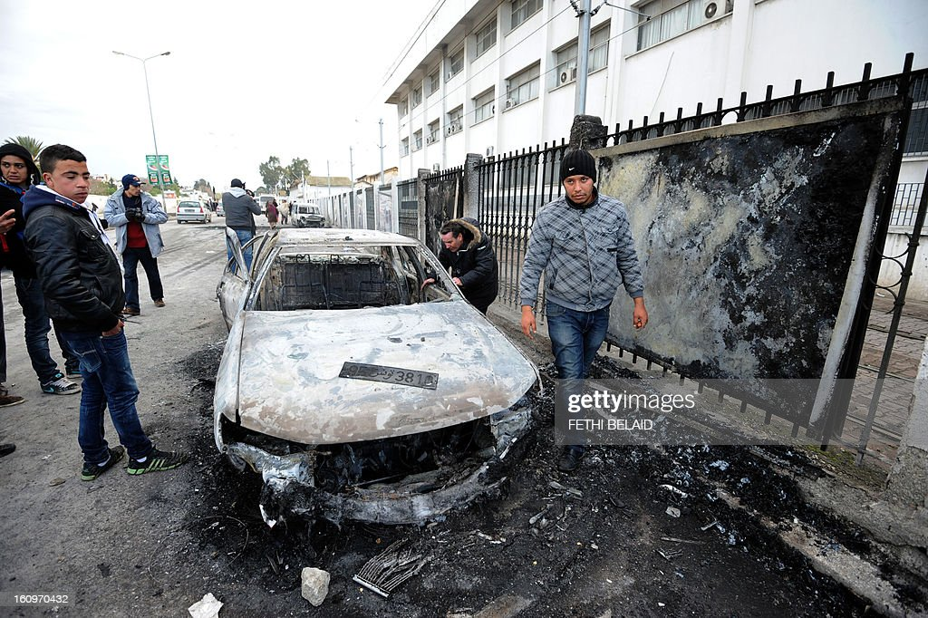 Tunisians inspect a burnt car that was set on fire by protesters following the funeral of assassinated opposition leader Chokri Belaid in Tunis on February 8, 2013. Tunisian police fired tear gas and clashed with protesters as tens of thousands joined the funeral of Belaid whose murder plunged the country into new post-revolt turmoil. AFP PHOTO/FETHI BELAID