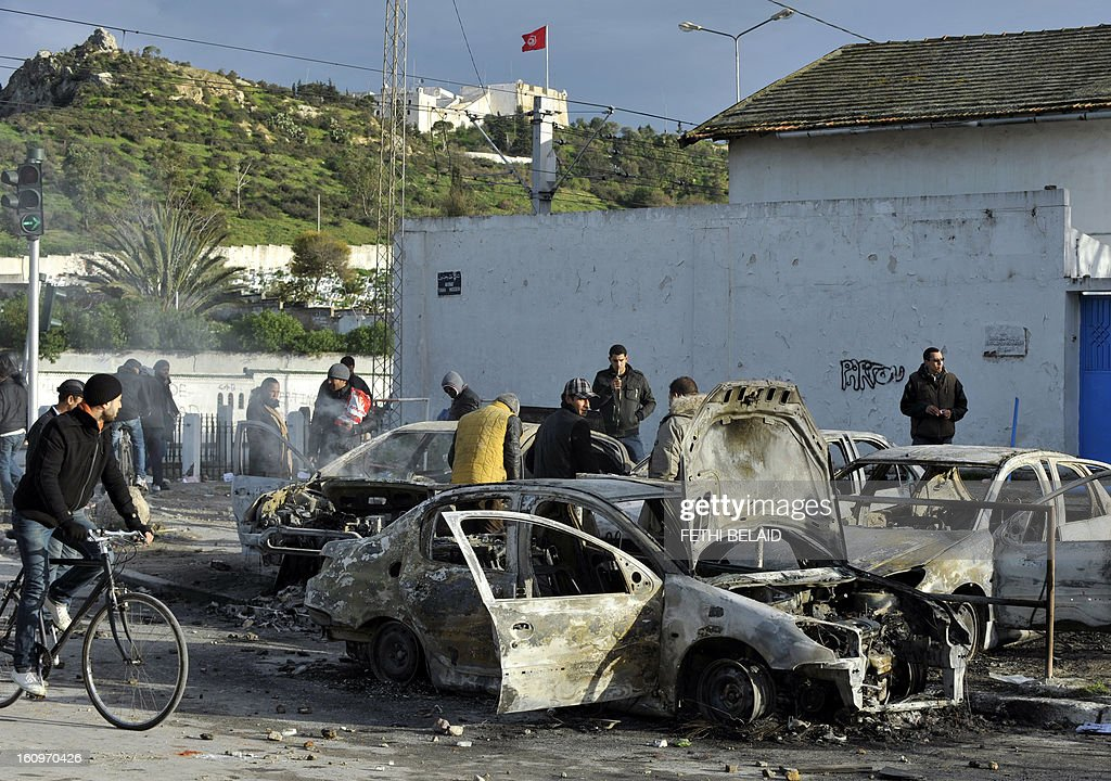 Tunisians inspect burnt cars that were set on fire by protesters following the funeral of assassinated opposition leader Chokri Belaid in Tunis on February 8, 2013. Tunisian police fired tear gas and clashed with protesters as tens of thousands joined the funeral of Belaid whose murder plunged the country into new post-revolt turmoil. AFP PHOTO/FETHI BELAID