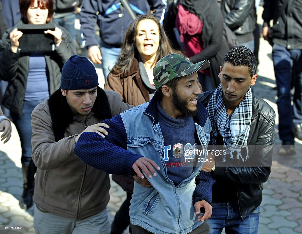 Tunisians restrain an Islamist student who was part of the group that attacked students of the Bourguiba Language Institute in the El Khadra neighbourhood, a Salafist bastion, of the capital Tunis, as they tried to prevent the filming of current Internet craze the 'Harlem Shake' on February 27, 2013. Salafist Muslims caused a fight when they tried to prevent the filming of the global online buzz, but the Islamists eventually withdrew and the students were able to film their production.
