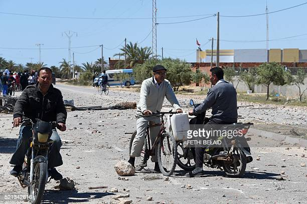 Tunisians ride in the locality of Laataya on the island of Kerkennah on April 15 2016 after residents covered the road with stones to prevent the...