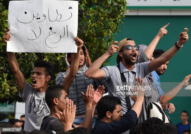 Tunisians shout slogans against foreign oil companies and the government as they hold a placard reading 'We don't give up' during a demonstration to...