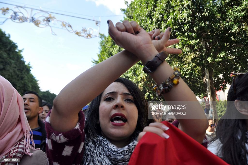 TOPSHOT Tunisians shout slogans during an antigovernment demonstration on January 20 2016 on Habib Bourguiba Avenue in Tunis in solidarity with...