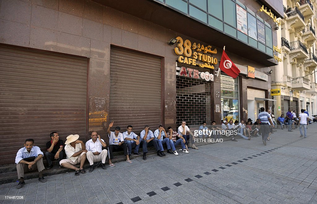 Tunisians sit in front of a closed cafe as the country marks a day of mourning after gunmen killed the leading opposition figure Mohamed Brahmi on July 26, 2013 in Tunis. Protests and a general strike swept Tunisia after gunmen killed a leading opposition figure, as under-fire authorities pointed to Al-Qaeda links behind the murder. AFP PHOTO / FETHI BELAID