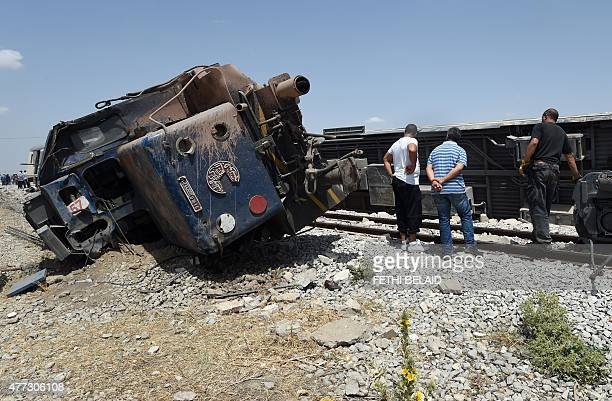 Tunisians surround the carriages of a train after it derailed following a collision with a lorry killing at least 17 people near the town of El Fahes...