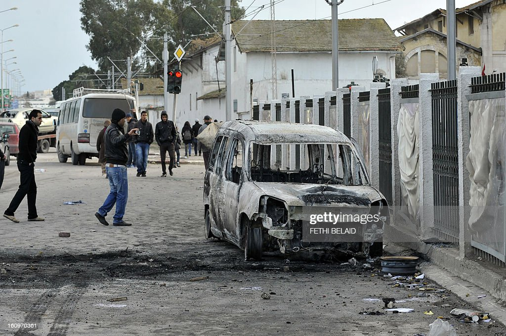 Tunisians walk past a burnt car that was set on fire by protesters following the funeral of assassinated opposition leader Chokri Belaid in Tunis on February 8, 2013. Tunisian police fired tear gas and clashed with protesters as tens of thousands joined the funeral of Belaid whose murder plunged the country into new post-revolt turmoil. AFP PHOTO/FETHI BELAID