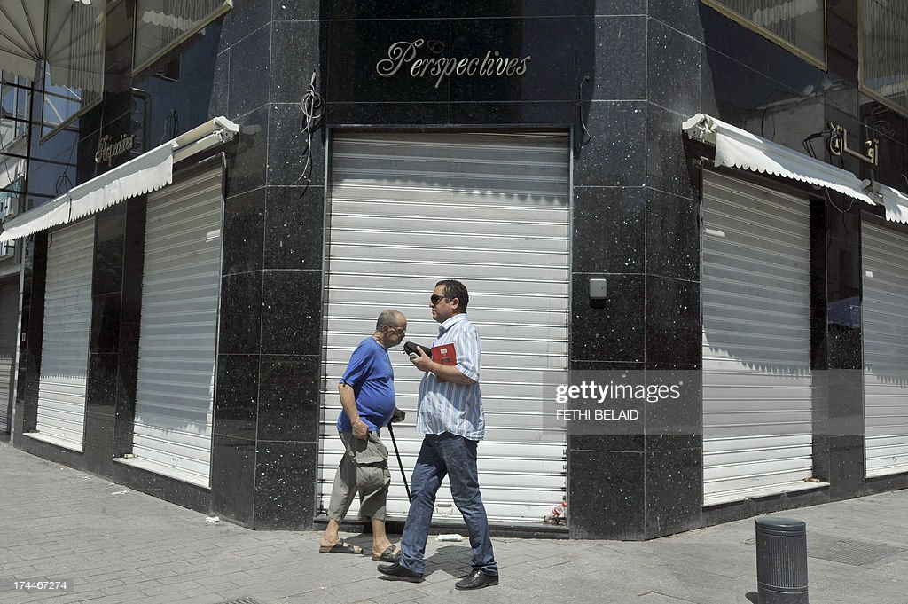 Tunisians walk past a closed shop as the country marks a day of mourning after gunmen killed the leading opposition figure Mohamed Brahmi on July 26, 2013 in Tunis. Protests and a general strike swept Tunisia after gunmen killed a leading opposition figure, as under-fire authorities pointed to Al-Qaeda links behind the murder.