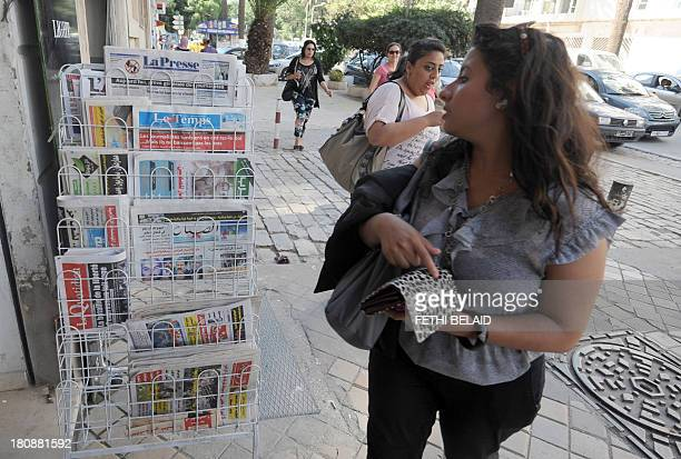 Tunisians walk past a newspaper stands during a sitin organized by journalists in Tunis on September 17 to protest pressures imposed on them by the...