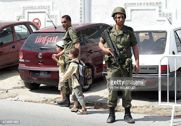 Tunisians walk past a soldier standing guard outside the Bouchoucha army barracks in Tunis on May 25 2015 after a soldier opened fire at his...