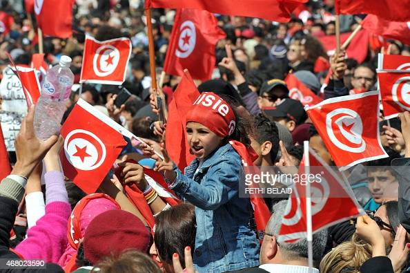 Tunisians wave their national flag and chant slogans during a march against extremism outside Tunis' Bardo Museum on March 29 2015 Thousands of...