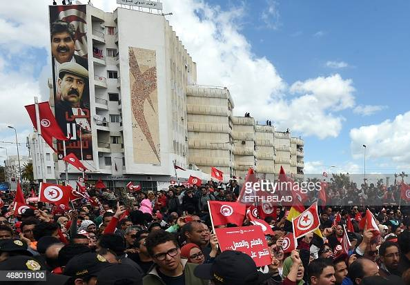 Tunisians wave their national flag during a march against extremism outside Tunis' Bardo Museum on March 29 2015 Thousands of Tunisians set off for a...