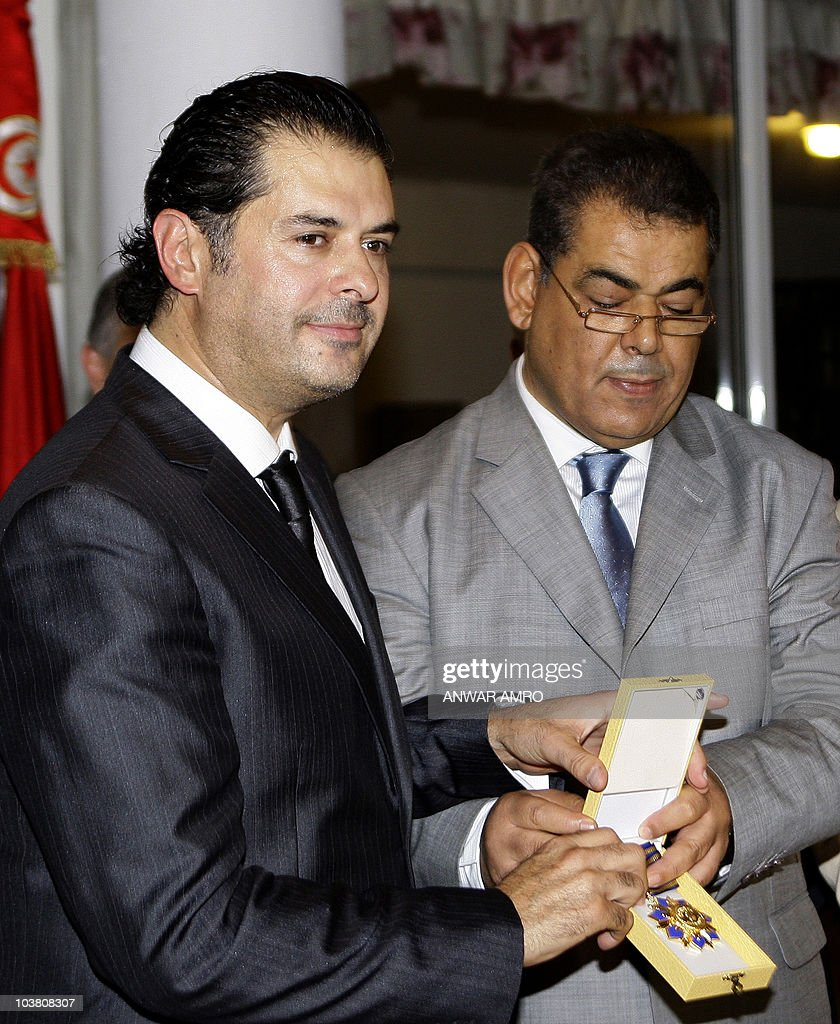 Tunisia's ambassador in Lebanon Samir Abdallah (R) hands Lebanese singer Ragheb Alama, who was in 2009 an honorary UN ambassador for environmental and climate issues, a medal from Tunisian President Zine El Abidine Ben Ali for his achievements in the field of music in the Arab world on September 3, 2010 at the Tunisian embassy in Beirut.