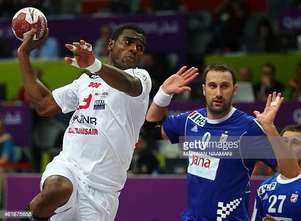 Tunisia's Amine Bannour takes a shot on goal as Croatia's Igor Vori during the 24th Men's Handball World Championships preliminary round Group B...