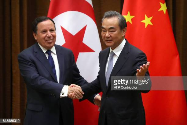 Tunisia's Foreign Minister Khemaies Jhinaoui and Chinese Foreign Minister Wang Yi shake hands before a meeting at the Ministry of Foreign Affairs in...