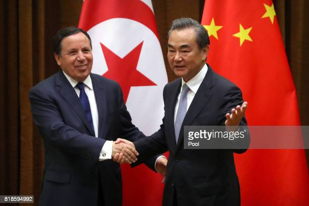 Tunisia's Foreign Minister Khemaies Jhinaoui left and Chinese Foreign Minister Wang Yi right shake hands as they pose for a photo before a meeting at...