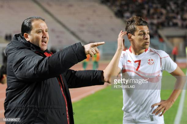 Tunisia's head coach Nabil Maaloul speaks with his striker Youssef Msakni during their FIFA 2014 World Cup qualifying match against Sierra Leone on...