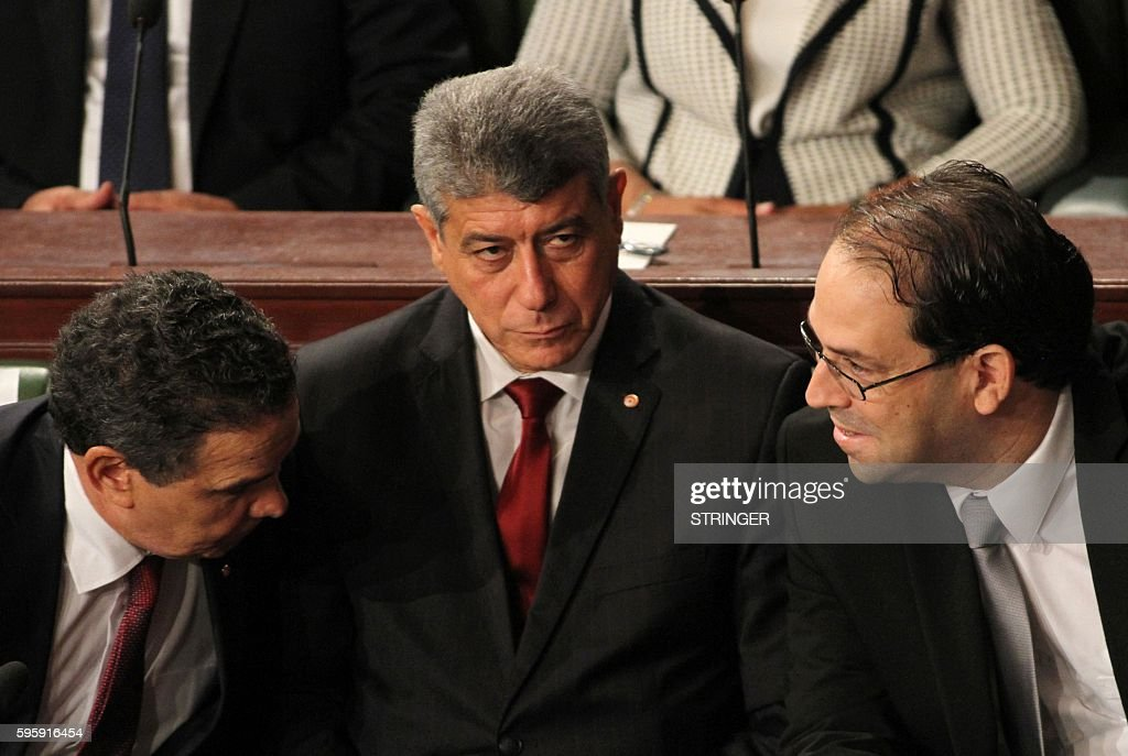 Tunisia's premierdesignate Youssef Chahed speaks with Tunisia's Defence Farhat Horchani as the Minister of Justice Ghazi Jribi listens on during a...