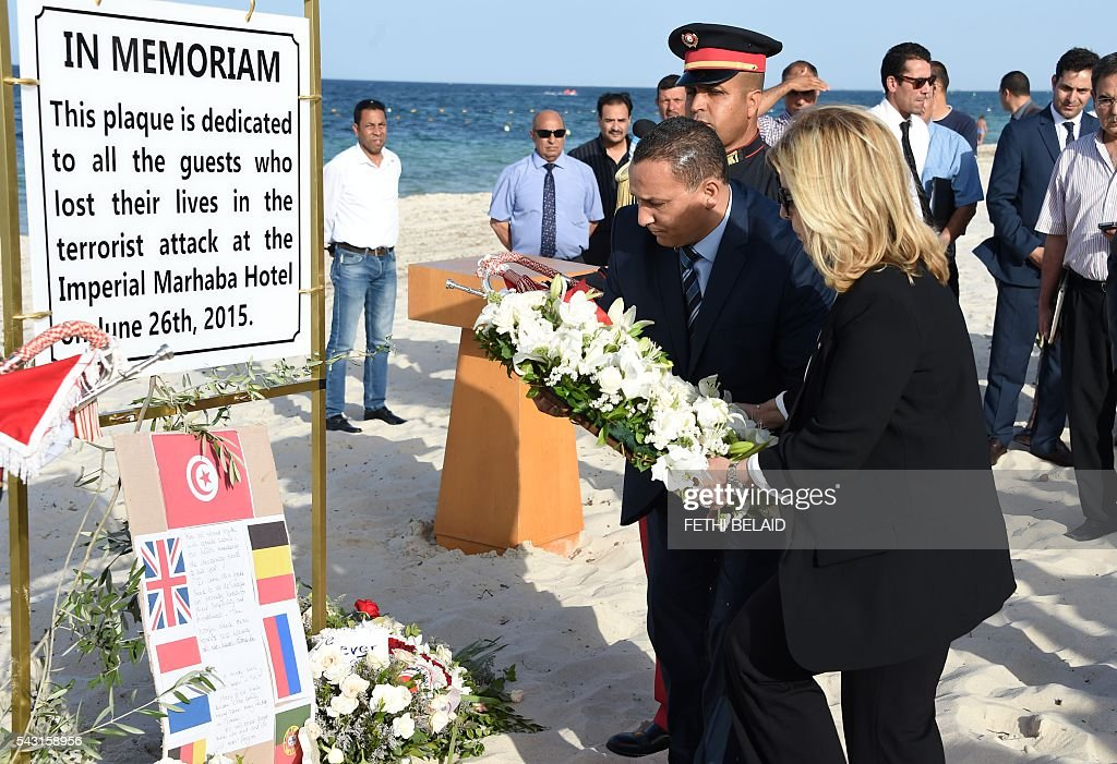 Tunisia's Tourism Minister, Salma Rekik Elloumi (R), lays a wreath of flowers on the beach on June 26, 2016, during a ceremony in memory of those killed a year ago by a jihadist gunman in front of the Riu Imperial Marhaba Hotel in Port el Kantaoui, on the outskirts of Sousse south of the capital Tunis. Tourists fled in horror on June 26, 2015 as a Tunisian gunman pulled a Kalashnikov rifle from inside a furled beach umbrella and went on a shooting spree outside the five-star hotel. 30 Britons were among 38 foreign holidaymakers killed in the attack. / AFP / FETHI
