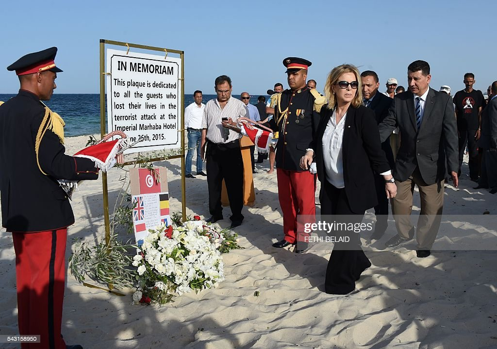 Tunisia's Tourism Minister, Salma Rekik Elloumi (2nd from R), prepares to lay a wreath of flowers on the beach on June 26, 2016, during a ceremony in memory of those killed a year ago by a jihadist gunman in front of the Riu Imperial Marhaba Hotel in Port el Kantaoui, on the outskirts of Sousse south of the capital Tunis. Tourists fled in horror on June 26, 2015 as a Tunisian gunman pulled a Kalashnikov rifle from inside a furled beach umbrella and went on a shooting spree outside the five-star hotel. 30 Britons were among 38 foreign holidaymakers killed in the attack. / AFP / FETHI