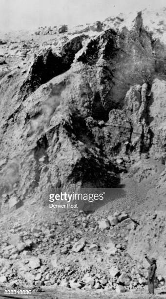 Several steady streams of dirt and small boulders trickle down vertical crevices in the shoulder of the moving mountain toward the Denver Rio Grande...