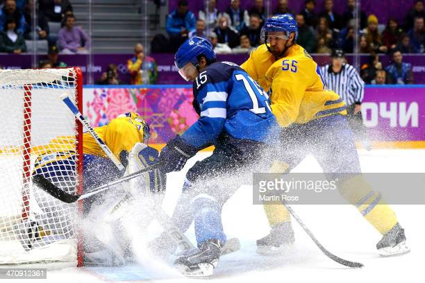 Tuomo Ruutu of Finland skates to the net against Henrik Lundqvist and Niklas Kronwall of Sweden in the second period during the Men's Ice Hockey...