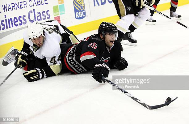 Tuomo Ruutu of the Carolina Hurricanes gets tangled up with Brooks Orpik of the Pittsburgh Penguins as he lunges for a loose puck during a NHL game...