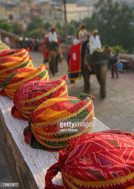 Turbans sit for sale as tourists ride atop elephants enroute to the 16th century Amber Fort November 19 2006 outside of Jaipur in the Indian state of...