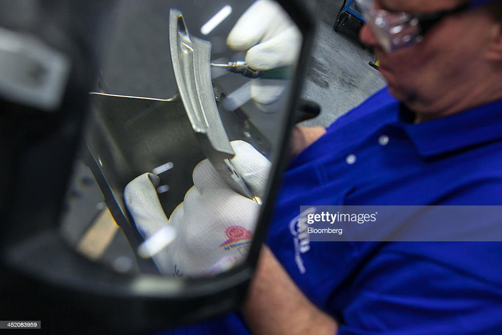 A turbine center frame for a GEnx engine, used in a Dreamliner Boeing 787 and 747-8 passenger jets, is seen through a magnifying glass as an employee works on the unit at the MTU Aero Engines factory in Munich, Germany, on Monday, Nov. 25, 2013. MTU Aero Engines Holding AG said it will eliminate jobs and cut costs to boost profitability as the German manufacturer predicted strong growth in sales of new engines next year. Photographer: Krisztian Bocsi/Bloomberg via Getty Images