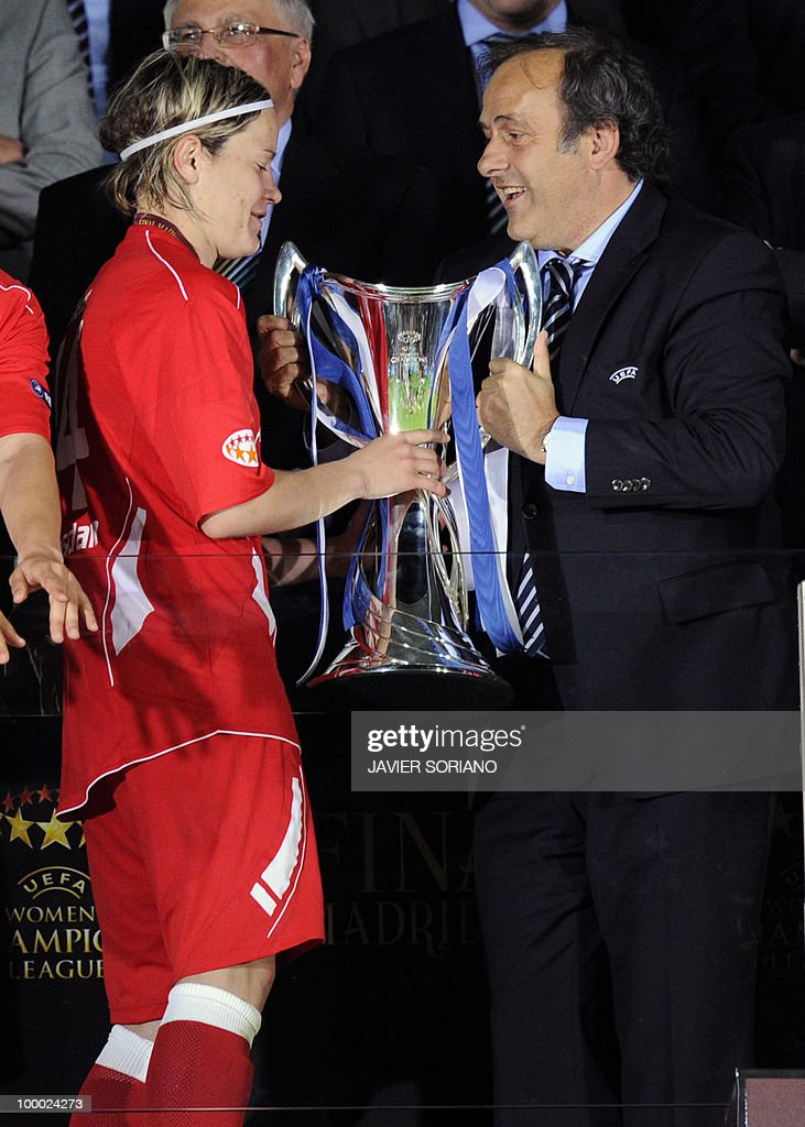 FFC Turbine Potsdam's midfielder Jennifer Zietz (L) receives the trophy from UEFA President Michel Platini after wining their UEFA women's Final Champions League football match against Olympique Lyonnais at Coliseum Alfonso Pérez on May 20, 2010 in Getafe.