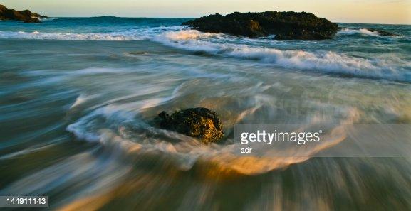 Turbulence water flowing around rocks at sunset : Stock Photo
