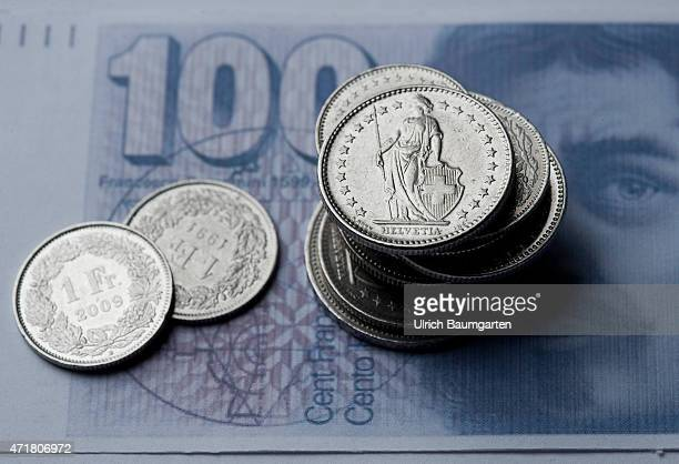 Turbulences around the Swiss franc Our picture shows coins of the Swiss currency on a counterfeit 100 franc banknote