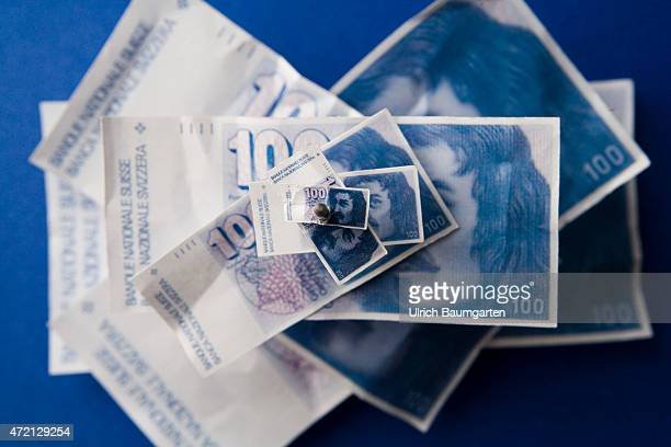 Turbulences around the Swiss franc Symbol photo on the topic devaluation revaluation Our picture shows impaled 100 franc banknotes in small and...