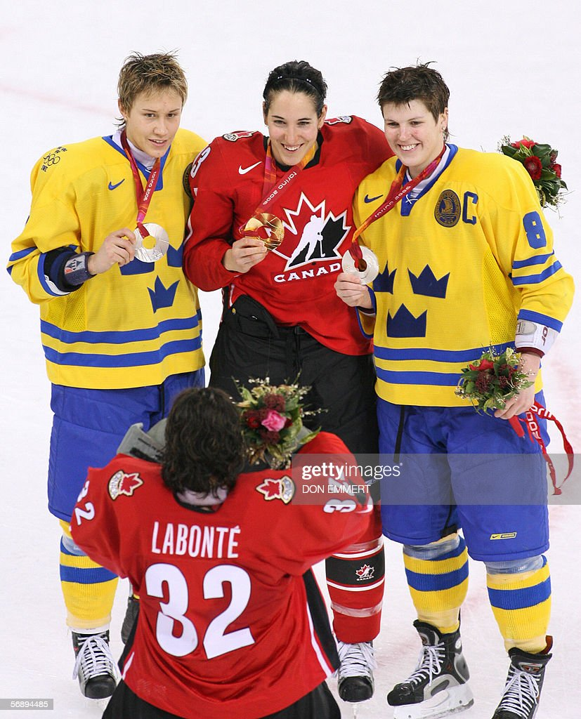 Canadian goalkeeper Charline Labonte (bottom) takes a picture of Canadian Caroline Ouellette (C), Swedish Erika Holst (R) and Maria Rooth at the end of the ice hockey women's gold medal game Sweden vs Canada at the 2006 Winter Olympics, 20 February 2006 at the Palasport Olimpico in Turin. AFP PHOTO DON EMMERT