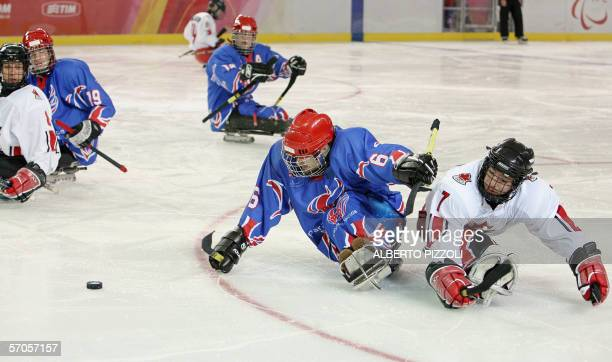 Canadian Marc Dorion challenges Karl Nicholson of Britain during their paralympics Ice Sledge Hockey match in Turin 11 March 2006 Canada won the...