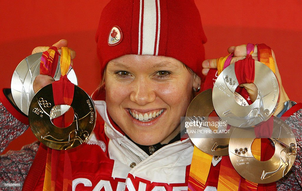 Canadian Speed Skater medallist Cindy Klassen poses with her medals during a 2006 Winter Olympics medals' ceremony in Turin 25 February 2006 AFP...