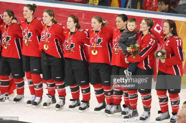 Canadians hockey players pose with their gold medals at the end of the ice hockey women's gold medal game Sweden vs Canada at the 2006 Winter...