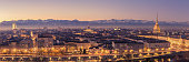 Turin, Italy: cityscape at sunrise with details of the Mole Antonelliana of Torino towering over the city. Scenic colorful light on the snowcapped Alps in the background. Panoramic view