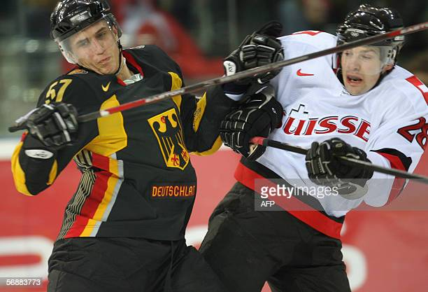 German Marcel Goc fights for the puck with Swiss Martin Pluss during the ice hockey men's preliminary round Germany vs Switzerland at the 2006 Winter...