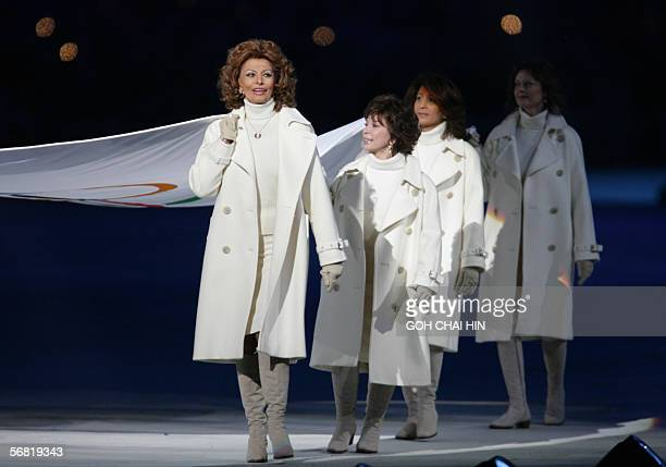 Italian actress Sophia Loren holds the Olympic flag 10 February 2006 at the Olimpico stadium in Turin during the opening ceremony of the 2006 Winter...